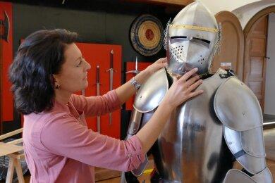 Museumsleiterin Claudia Glashauser kümmert sich um die neuen Ritter auf Burg Scharfenstein. Beim Aufbau werden etwa 20 Figuren, sieben davon samt Rüstung, in Stellung gebracht.