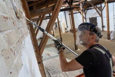 Michael Lienemann streicht die Wände im Güterschuppen - die Maske schützt seine Augen vor Kalkspritzern.