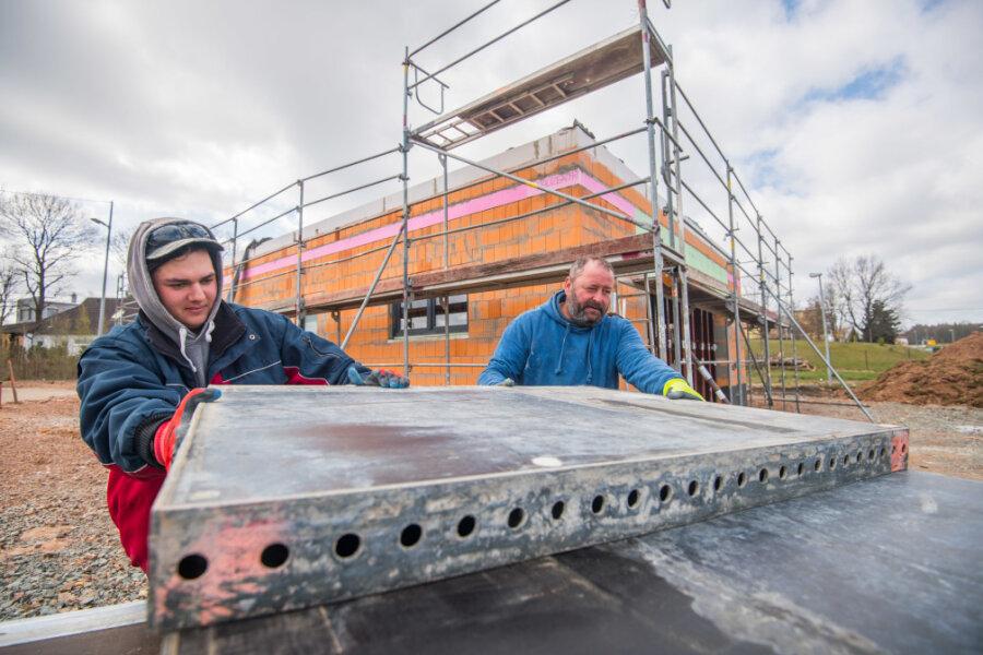 An der Stollberger Straße 31 in Neukirchen entsteht eine Eismanufaktur. Die Inbetriebnahme ist für diesen Sommer geplant. Lukas Müller und Thomas Eckhart vom Baugeschäft Sehm aus Tauscha bei Penig beim Verladen von Schaltafeln für Beton.