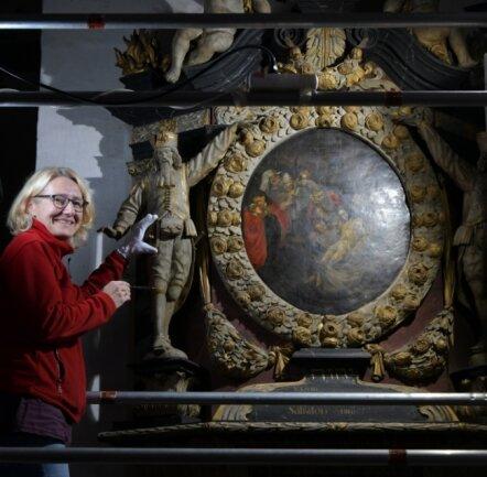 Restauratorin Susanne Mayer zeigt den Bergmann und die Stelle des Säbels am Theodor Siegel Epitaph. Die Arbeit aus Holz und Stein ist im Dom St. Marien zu Freiberg zu finden.