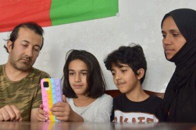 Assadullah (links) und Media Khaleqian (rechts) mit zwei ihrer insgesamt fünf Kinder, Ruhalla (Mitte rechts) und Fatima. Sie schauen sich täglich im Internet Nachrichten und Videos über den Zustand ihres Heimatlandes an, seitdem die Taliban dort die Macht ergriffen haben.