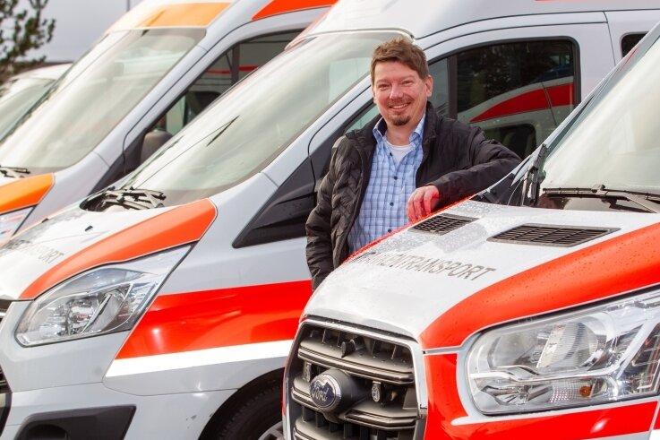 Geschäftsführer Jens Leistner vom Rettungszweckverband Südwestsachsen inmitten von Krankentransportwagen. Allein 23 neue KTW des Modells Ford Transit hat der RZV Ende 2020 angeschafft.