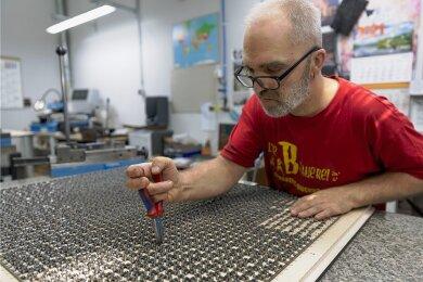 Diese Stanzform aus dem Werk der Marbach-Gruppe in Geyer kommt später bei der Produktion eines 2000-Teile-Puzzles zum Einsatz. Die Arbeit an dem Einzelstück dauert mehrere Wochen. Im Bild: Udo Küchler.