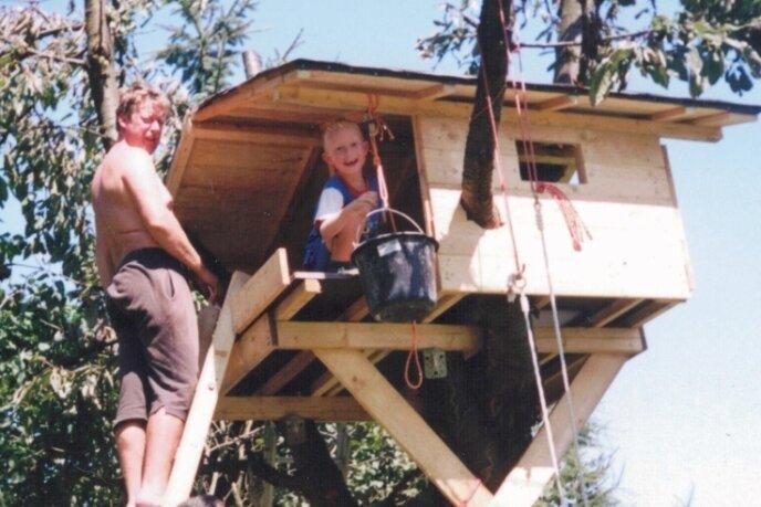 """Vater Hendrik (auf der Leiter) und Sohn Bruno beim gemeinsamen Arbeiten am Häuschen. Es """"wuchs"""" 2002 auf einem alten Baum, der geeignete Äste hatte, und wurde vor allem innen im Lauf der Jahre immer weiter verbessert."""