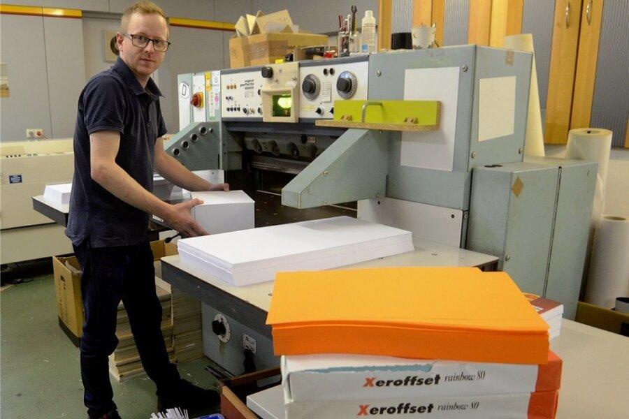 Fürs Papier müssen Unternehmen wie Concepcion Seidel (im Bild Jan Seidel an der Schneidemaschine) deutlich mehr bezahlen. Für Großaufträge muss monatelang vorbestellt werden.