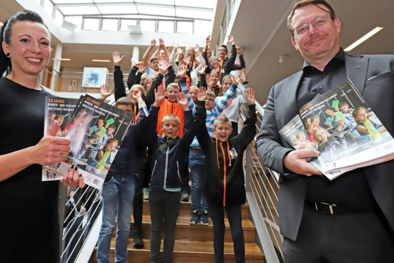 Franziska Schwehm und Freibergs OB Sven Krüger präsentieren gemeinsam mit den Mitgliedern des Kinder- und Jugendparlaments die Chronik zum 25. Kipa-Geburtstag.