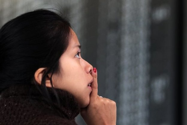 Eine Frau steht ratlos vor einer Fluginformationstafel, auf der die bestreikten Lufthansa-Flüge angezeigt werden.