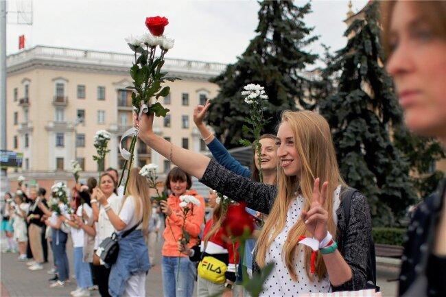 Sie halten Blumen in der Hand und zeigen Peace-Zeichen: Aktivistinnen der Opposition bei einem Protest auf dem Siegesplatz in Minsk. Werden sie dafür bezahlt?