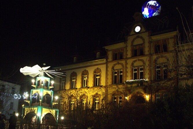 Die beleuchtete Pyramide vor dem Pausaer Rathaus. Auf dem Gebäude prangt die Weltkugel.