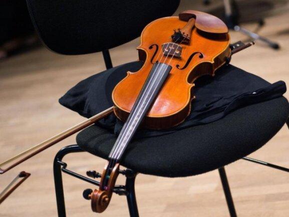 Eine Geige liegt in einer Probenpause im Konzertsaal der Philharmonie Bad Reichenhall auf einem Stuhl.