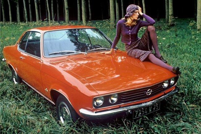 """Ein Model posiert auf der Motorhaube eines neuen Opel """"Manta"""" in knallroter Lackierung (Aufnahme von 1970)."""