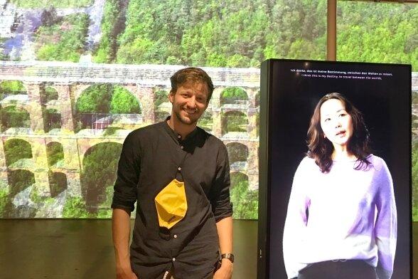 Christian Hunziker, wissenschaftlicher Mitarbeiter der Landesausstellung, neben der virtuell anwesenden Modedesignerin Saruul Fischer. Im Hintergrund auf großer Leinwand die Göltzschtalbrücke.