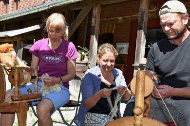 Mitarbeiter des Vogtländischen Freilichtmuseums in Landwüst und Eubabrunn haben sich mit dem alten Handwerk Spinnen vertrautgemacht. Angeleitet wurden sie dabei von Andrea und Olaf Born aus Striegistal. Andrea Born (links), Franziska Waldmann und Norman Schöbel.