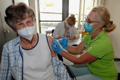 Krankenschwester Katja Dorn verabreicht Renate Wutzler die erste Impfung, hinten Ärztin Noreen Drechsler.