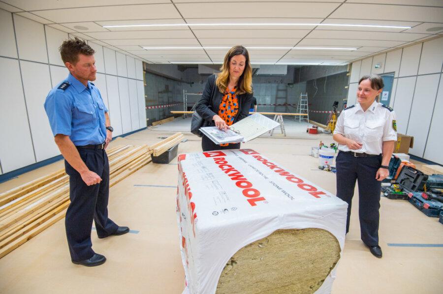 Schießtrainer Mathias Melzer, Heike Krenkel, die Niederlassungsleiterin der SIB Zwickau, und Marika Schwanitz, die Leiterin der Polizeifachschule, überzeugen sich in der Schießanlage vom Baufortschritt.