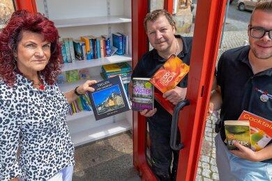 Auf dem Treuener Markt steht jetzt eine Büchertauschzelle. Bürgermeisterin Andrea Jedzig, ließ sich von den Kulturbanausen Maik Strauß und Lukas Lorber (rechts) zeigen, welche Bücher man dort finden kann.