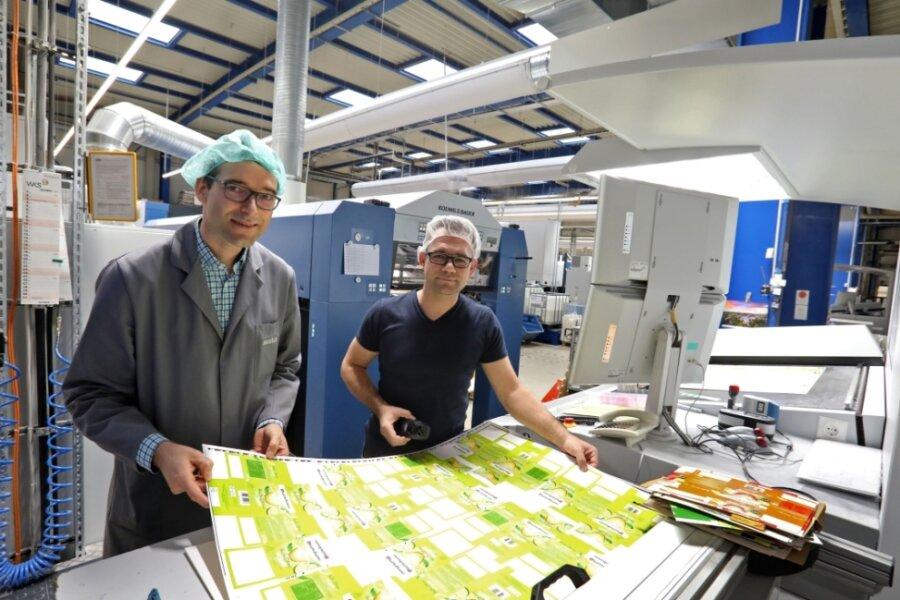 Geschäftsführer Ulli Mugler (links) und Offsetdrucker Daniel Dietrich (li.) prüfen die Druckqualität der Bögen für die Zitronentee-Verpackungen. Dank der neuen Klimaanlage herrscht an der Maschine immer frische Luft.