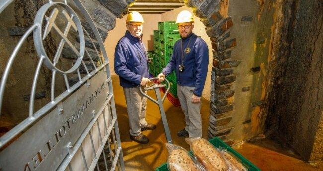 Bäcker mit Helm und Geleucht: Winfried (l.) und Tobias Nönnig bringen den Bergmannsstollen ins Lager. 15.000 Stollen werden in der Bäckerei und Konditorei jährlich gebacken.