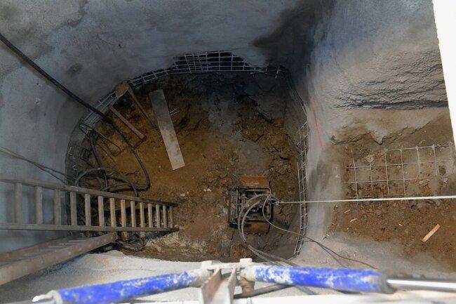 Der Tagebruch, der bei Straßenbauarbeiten an der Himmelfahrtsgasse in Freiberg entdeckt wurde, ist derzeit acht Meter tief, gemessen von der Oberkante der Straße. Über eine Fahrt (für Nicht-Bergleute: das ist die Leiter) klettert der Bergmann nach unten und befüllt die Transportkübel mit Abraum.
