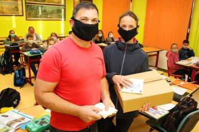 Tejas und Mandy Hirsch haben die Masken an die Sahnschule übergeben. Sie unterstützen zudem eine Grundschule in Meerane.