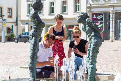 """Florian Wißgott, Chiara Warg und Eva-Maria Gey (von links), Mitarbeiter der """"Freien Presse"""" in Plauen, haben das neue """"Escape Game"""" für die Stadt getestet. Der Startpunkt der Geschichte ist auf dem Altmarkt."""