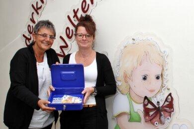 """Ines Ambos (l.) und Heike Baum aus der Kinderkrippe """"Weltentdecker"""" freuen sich über die Spenden, die ihre Geldkassette für einen guten Zweck füllen."""