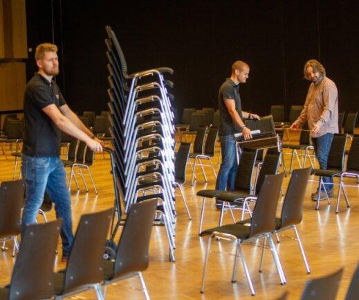 Nach dem großen Stühlerücken, um Abstandsregeln einzuhalten, ist coronabedingt erneut die große Stille in der Festhalle eingezogen. Einrichtungschef Ronny Bley (rechts) sowie Mitarbeiter Alexander Poppitz (links) und Marc Rost ringen nun um ein neues Konzept.