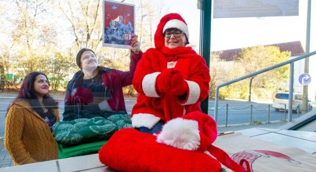 Doritta Korte ist schon voll auf Weihnachten eingestimmt: Die ins Kostüm geschlüpfte Vogtländerin will mit Julia Postier (links) und anderen Mitgliedern des Colorido-Vereins Plauen zu einem besonderen Adventskalender verhelfen. Wandgestalter Slexnenskat (Mitte) wird einer von über 20 Künstlern sein, die die Schaufensteraktion unterstützen.