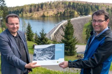 LTV-Betriebsleiter Frank Hunger (r.) übergibt Ingolf Wappler, Bürgermeister von Pockau-Lengefeld, die letzte der Infotafeln für den Rundweg um die Mauerkrone der Talsperre Saidenbach.