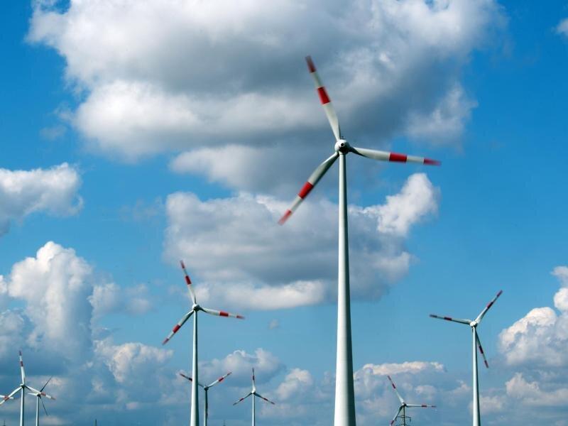 Windräder drehen sich unter dem Wolkenhimmel auf einem Feld.