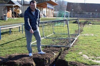Marcus Röll steht an der Übergangsstelle der Zuleitung zur Ringleitung auf dem Spielfeld.