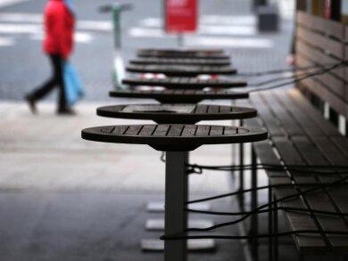 Mit Stahlschnüren gesichert sind die Tische eines wegen der Corona-Beschränkungen geschlossenen Restaurants in Augsburg.