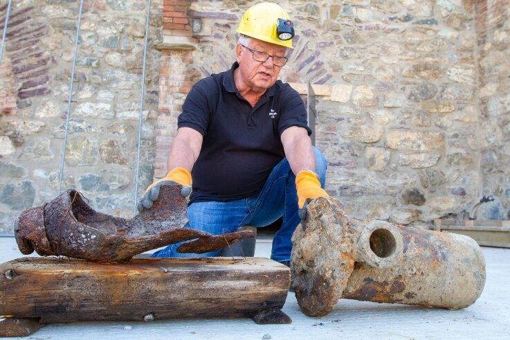 Links die Reste einer Bombe, rechts das Teil, das im Schlosshang begraben lag: Heimatforscher Gert Müller legt beides nebeneinander.