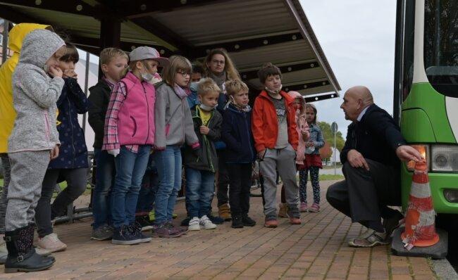 Wäre der Kegel ein Kind gewesen, sähe es für dieses nicht gut aus. Busfahrer Steffen Schukat erklärt den Kindern, worauf sie an der Haltestelle zu achten haben. Die Busschule fand am Oelsnitzer Bahnhof statt.