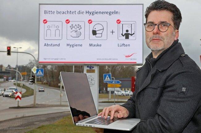 Sascha Neef bedient eine LED-Werbetafel von Comedia Concept an der Oskar-Arnold-Straße.