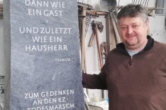 Der Oelsnitzer Steinmetzmeister Michael Ballmann mit der in seiner Werkstatt entstandenen übermannsgroßen Stele aus Theumaer Schiefer. Christoph Stölzel, Eichigts scheidender Bürgermeister, hat sie finanziert. Nächsten Samstag wird der Gedenkstein in Bergen aufgestellt.