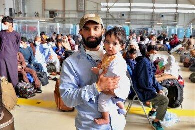 Zubair Hakimi mit seiner elfmonatigen Tochter Usra in einer Halle auf der US-Luftwaffenbasis im pfälzischen Ramstein. Der 26-Jährige hat auf der Nato-Basis in Kabul als Techniker für die Amerikaner gearbeitet. Er gehört zu den tausenden Afghanen, welche nach Deutschland ausgeflogen wurden und nun auf ihren Weiterflug in die USA und andere Länder warten.