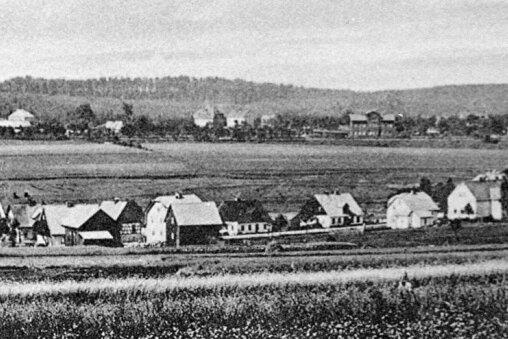 Das Foto ist um 1930 entstanden. Im Vordergrund: Böhmisch Reizenhain. Im Hintergrund: das sächsische Reitzenhain. Rechts am Bildrand ist der Bahnhof zu sehen.