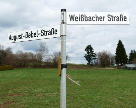 Über die Fläche hinter diesen beiden Straßenschildern in Dittersdorf soll künftig eine kleine Straße zu den neuen Grundstücken führen. Der Bereich wird derzeit landwirtschaftlich genutzt, ein Teil dient zudem als Kleingartenbereich sowie als Lagerfläche für den Bauhof.