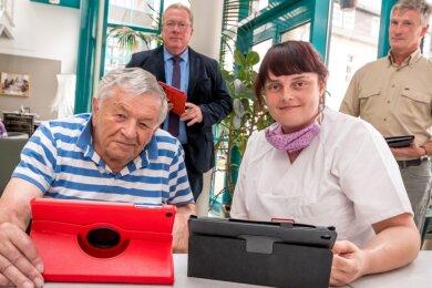 Jens Kaltofen (hinten, l.) und Peter Zehrt verfolgten, wie sich Bewohner Harald Kaden und Wohnbereichsleiterin Corinna Schade nach der Übergabe mit den Tablets vertraut machten.