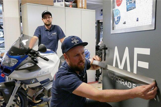 """Auch an der Eingangstür seiner Werkstatt, die er zusammen mit Mechaniker Ralf Kaulich betreibt, muss Inhaber Markus Fleischer den Streifen seines Firmenlogos überkleben. Die """"M-Farben"""" dürfen nicht mehr zu sehen sein."""