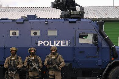 """SEK-Beamte vor einem der beiden Panzerwagen """"Survivor R"""" der sächsischen Polizei."""