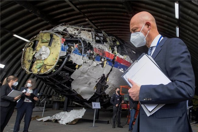 Der vorsitzende Richter Hendrik Steenhuis (r) und andere Prozessrichter und Anwälte betrachten das rekonstruierte Wrack von Malaysia Airlines Flug MH17, auf dem Militärflugplatz Gilze-Rijen.