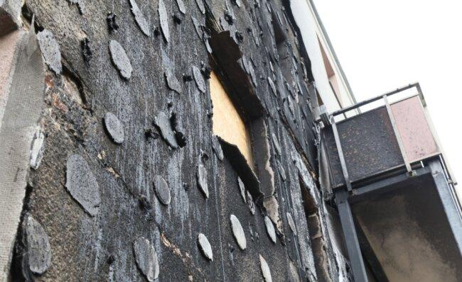 Die weggebrannte Dämmung an der Fassade hat häßliche Klebeflecken hinterlassen, alles ist verrußt.