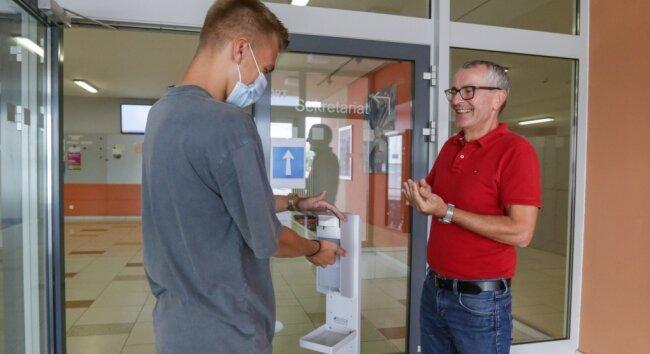 Direktor Torsten Kulakow (rechts) steht mit Erwin Biener, Schüler der zehnten Klasse, am Desinfektionsspender im Eingangsbereich der Sportoberschule. Hier müssen sich die Schüler die Hände desinfizieren, bevor sie in ihre Klassenräume gehen können.