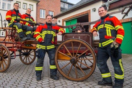 Michel Hummel, Thomas Leichsenring, Jörg Axmann und Carsten Brandt (von links) von der Freiwilligen Feuerwehr und dem Feuerwehrverein Hohndorf mit ihrer historischen Abprotzspritze. Das Löschgerät, das von 1885 bis 1936 im Dienst war, soll jetzt restauriert werden.