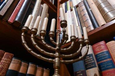"""Ein Chanukkaleuchter steht in der """"Stefan und Inge Heym Arbeitsbibliothek"""" vor den Büchern."""