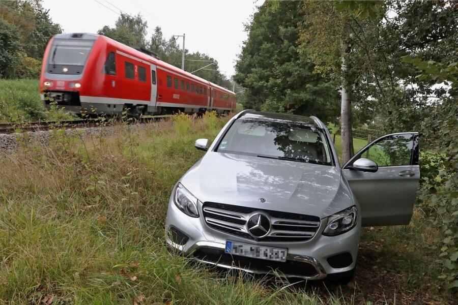 Auf einem Feldweg zwischen Hecke und Bahnlinie steht der gestohlene Mercedes.
