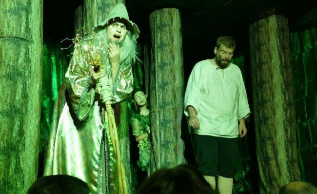 Das Glasmännlein (links), gespielt von Henry Merbeth, warnt Peter, gespielt von Philipp Wenzel, davor, zu gierig zu werden. Ein Waldgeist beobachtet die Szene.