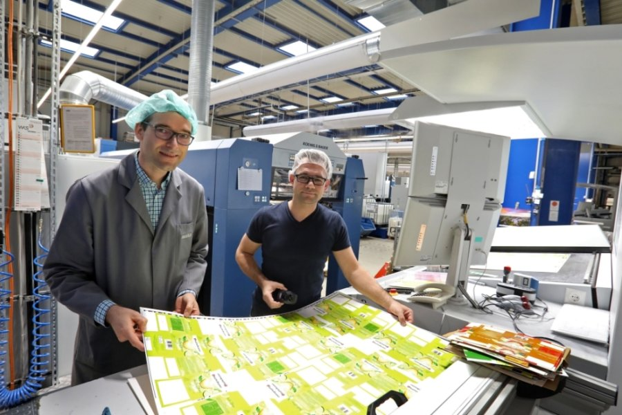 Geschäftsführer Ulli Mugler (links) und Offsetdrucker Daniel Dietrich (li.) prüfen die Druckqualität der Bögen für die künftigen Zitronentee-Verpackungen. Dank der neuen Klimaanlage herrscht an der Maschine immer frische Luft.
